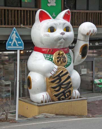The Waving Cat The Waving Cat There is one story that illustrates how something can come to be recognized as a kami. Once an emperor was traveling in a rainstorm.